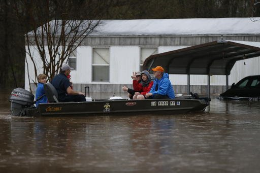 (AP Photo/Gerald Herbert). People motor through rising floodwaters at the Pecan Valley Estates trailer park in Bossier City, La., Wednesday, March 9, 2016.