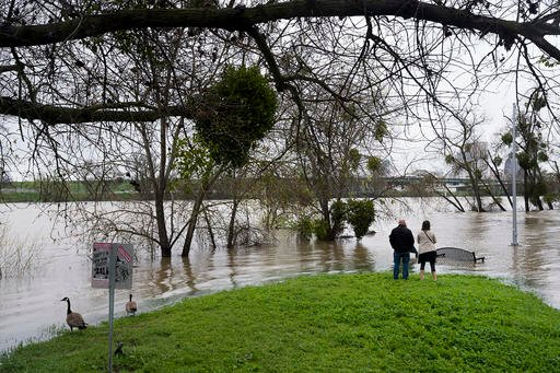 (KCRA3, KXTV10, KOVR13, KUVS19, KMAZ31, KTXL40). Andy Laughlin and Katie Sarber, of West Sacramento, look at the rising level of the Sacramento River at the Broderick Boat Ramp on Sunday, March 13, 2016 in West Sacramento, Calif.