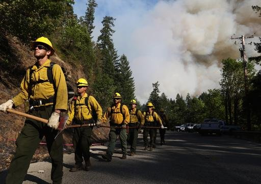 (Michael Sullivan/The News-Review via AP, file). FILE--In this July 28, 2015 file photo, Department of Forestry firefighters prepare for work at the Cable Crossing Fire near Glide, Ore.