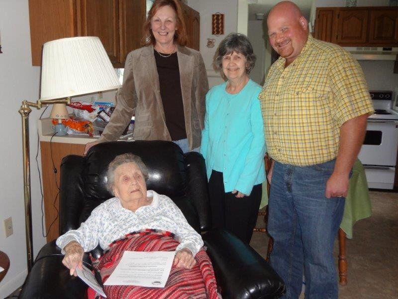 """Mrs. Florine Williams (seated) receives a Resolution from the Mayor and Council of Alderson declaring her a """"Centenarian of the Town of Alderson.""""  (L to R standing) Betty Thomas, Recorder; Ann Eskins, Council Member; and Travis Copenhaver, Mayor."""