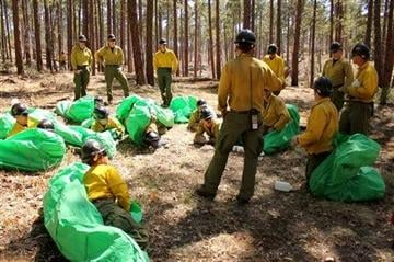 (AP Photo/Cronkite News, Connor Radnovich). In this 2012 photo provided by the Cronkite News, Phillip Maldonado, a squad leader with the Granite Mountain Hotshots, trains crew members on setting up emergency fire shelters.