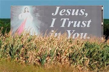 AP Photo/Nati Harnik). In this Aug. 27, 2013, photo corn drying up prematurely grows in front of a billboard in a field near Davey, Neb.