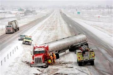 (REV-SHARE). A tanker truck is tended to by firefighters after sliding off the snowy highway near mile marker 48 on Interstate 90 in Piedmont, S.D., Tuesday afternoon, Dec. 3, 2013. (AP Photo/Rapid City Journal, Chris Huber) .