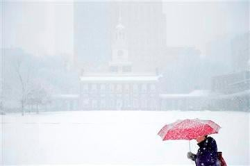 (AP Photo/Matt Rourke). A woman walks past Independence Hall during a winter snowstorm Tuesday, Dec. 10, 2013, in Philadelphia.
