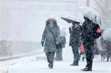(AP Photo/Matt Rourke). Commuters wait on a train during a winter snowstorm Tuesday, Dec. 10, 2013, in Philadelphia.