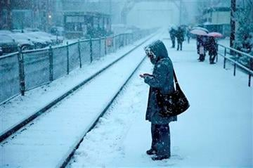 (AP Photo/Matt Rourke). A commuter waits on a train during a winter snowstorm Tuesday, Dec. 10, 2013, in Philadelphia.