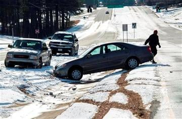 (AP Photo/John Amis). Richard Uzoma returns to his car after he lost control and abandoned it overnight along with other vehicles which couldn't traverse the ice build up on Peachtree Industrial Blvd.