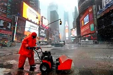 (AP Photo/Jason DeCrow). A worker clears slush from a street as snow falls Monday, Feb. 3, 2014, in New York's Times Square.