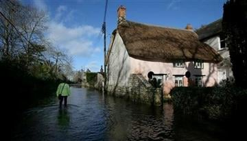 (AP Photo/Alastair Grant). In this photo taken Sunday Feb. 2, 2014, an emergency support worker wades through floodwater in Thorney in Somerset, England.