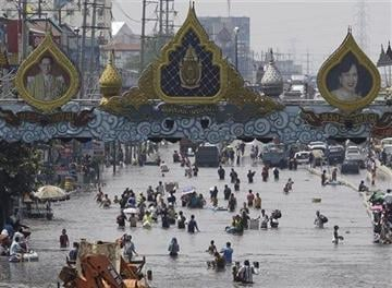 © (AP Photo/Aaron Favila, File). FILE - In this Oct. 21, 2011 file photo, resident wade through floods in Rangsit district on the outskirts of Bangkok, Thailand.