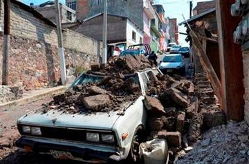 (AP Photo/Alejandrino Gonzalez). A parked car suffered damage when a adobe wall collapsed on it after a strong earthquake shook Chilpancingo, Mexico, Friday morning, April 18, 2014.