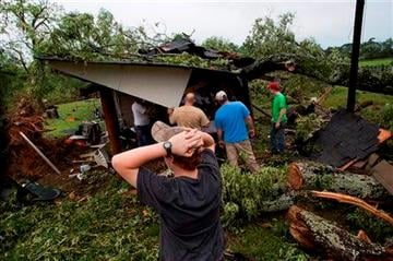 (AP Photo/Opelika-Auburn News, Albert Cesare). People work on clearing a tree off a shed after a storm in Smiths Station, Ala., Tuesday, April 29, 2014.