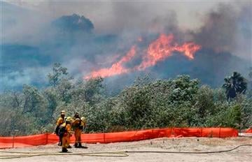 (AP Photo). Flames grow as a wild fire burns out-of-control in the north county area of San Diego Tuesday, May 13, 2014, in San Diego.