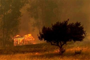 AP Photo/Gregory Bull). Fire engulfs a structure during a wildfire Thursday, May 15, 2014, in Escondido, Calif.