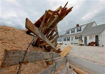 (AP Photo/Patrick Semansky, File). FILE - This Nov. 1, 2012 file photo shows a pile of sand and debris sitting near a house that was damaged by superstorm Sandy in Brant Beach, N.J.