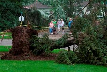 (AP Photo/The Grand Rapids Press, Chris Clark). Leisure Acres condominium residents make their way through the damaged area in Kentwood, Mich.