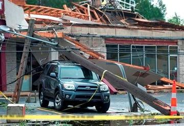 (AP Photo/The Grand Rapids Press, Chris Clark). Langley Plaza is damaged along with a vehicle after an overnight storm passed through in Grand Rapids, Mich.