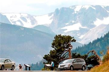 (AP Photo/Brennan Linsley). A family stops at a pull off on Trail Ridge Road, inside Rocky Mountain National Park just west of Estes Park, Colo., Monday, July 14, 2014.