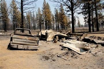 (AP Photo/The Herald and News, Lacey M Jarrell). The shell of a burned pickup truck is all that remains Tuesday, July 15, 2014, at one of a dozen home sites in the Moccasin Hills subdivision north of Sprague River, Ore.