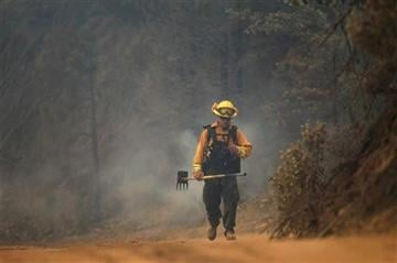 (AP Photo/Record Searchlight, Andreas Fuhrmann). A firefighter walks on Bully Choop Road on Wednesday, July 16, 2014, on the Bully Fire near Ono, west of Redding, Calif.