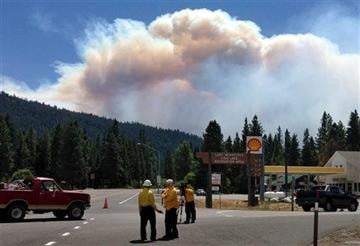 (AP Photo/The Seattle Times, Mike Siegel). Plumes of smoke from the Leavenworth wildfire arc in the sky as seen from Highway 2 at Highway 207, west of Leavenworth, Wash. on Thursday, July 17, 2014.