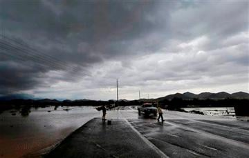 (AP Photo/Matt York). A city of Phoenix official blocks a closed section of road as flash flood waters overrun Skunk Creek through the Sonoran Desert, Tuesday, Aug. 19, 2014, in northwestern Phoenix.