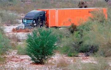 (AP Photo/Matt York). A tractor trailer drives through flash flood waters that overran Skunk Creek, Tuesday, Aug. 19, 2014, in northwestern Phoenix.
