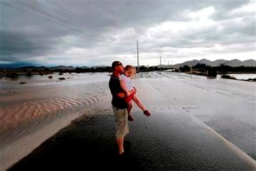 (AP Photo/Matt York). Josh Groves, and his daughter Abagayle Groves, 3, wait to cross the road as flash flood waters overrun Skunk Creek through the Sonoran Desert, Tuesday, Aug. 19, 2014, in northwestern Phoenix.