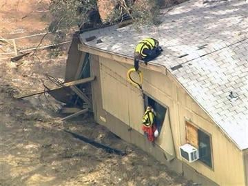 (AP Photo/ABC15 TV). In this image made from a video provided by ABC15 TV, a rescue worker from a helicopter reaches down to residents of a flooded house in New River, Ariz., north of Phoenix, Tuesday, Aug. 19, 2014.