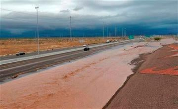 (AP Photo/Matt York). Flash flood waters from the overrun Skunk Creek flood I-10, Tuesday, Aug. 19, 2014, in northwestern Phoenix.