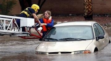 (AP Photo/Arizona Daily Star, Kelly Presnell). Tucson Fire Department personnel use a ladder truck to rescue a woman from a car stranded in rising flood waters in east Tucson, Ariz., Tuesday, Aug. 19, 2014.