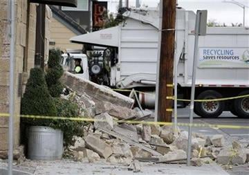 (AP Photo/Eric Risberg). A garbage truck moves past rubble in front of the earthquake damaged Vintners Collective multi-winery tasting room Monday, Aug. 25, 2014, in Napa, Calif.