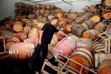 AP Photo/Eric Risberg). Cellar worker Daniel Nelson looks over toppled barrels of Cabernet Sauvignon following an earthquake at the B.R.