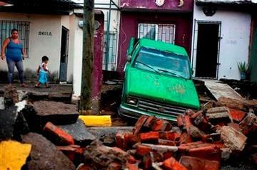 (AP Photo/Felix Marquez). A woman looks at the damage after part of a street and a home collapsed due to heavy rains in the Gulf port city of Veracruz, Mexico, Tuesday Sept. 2, 2014.