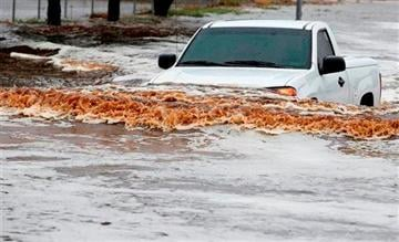 AP Photo/Ross D. Franklin). A pick-up truck driver tries to navigate a severely flooded street as heavy rains pour down Monday, Sept. 8, 2014, in Phoenix.