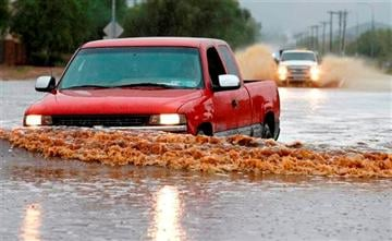 (AP Photo/Ross D. Franklin). Drivers attempt to navigate their vehicles through severely flooded streets as heavy rains pour down Monday, Sept. 8, 2014, in Phoenix.
