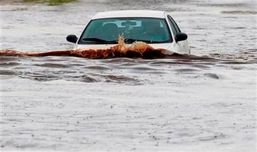 (AP Photo/Ross D. Franklin). A driver tries to navigate a severely flooded street as heavy rains pour down Monday, Sept. 8, 2014, in Phoenix.