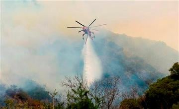 AP Photo/Orange County Register, Sam Gangwer). An Orange County Fire Authority helicopter drops a load of water on a brush fire in Silverado Canyon in Orange County, Calif. on Friday, Sept. 12, 2014.