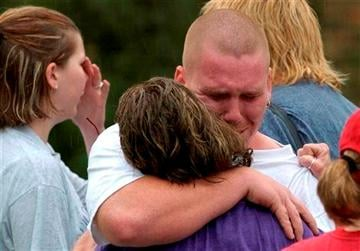(AP Photo/The Houston Chronicle, Steve Ueckert). In this June 25, 2004 photo Sherry Jones, center, is hugged by her her son Landon Jones as authorities search for her younger son, Logan Jones, 13, during heavy rains in Houston, Texas.