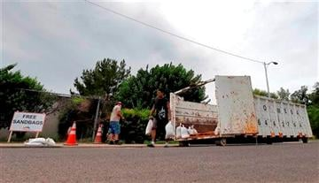 (AP Photo/Matt York). Mesa residents take free sandbags to protect their homes, Tuesday, Sept. 16, 2014 in Mesa, Ariz.