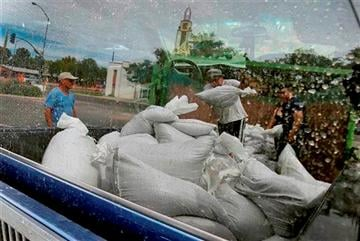 (AP Photo/Matt York). Mesa residents, reflected in a truck window, take free sandbags to protect their homes, Tuesday, Sept. 16, 2014 in Mesa, Ariz.