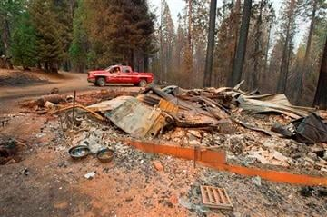 (AP Photo/The Sacramento Bee, Randall Benton, File). FILE - In a Friday, Sept. 19, 2014 file photo, a truck passes one of several homes that burned in the recent King fire near Icehouse in El Dorado County, Calif.
