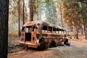 (AP Photo/The Sacramento Bee, Randall Benton). A burned out bus is shown near one of several homes that burned in the recent King fire near Icehouse in El Dorado County on Friday, Sept. 19, 2014.