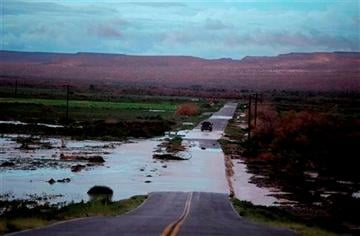 (AP Photo/John Locher,File). FILE - In this Monday, Sept. 8, 2014 file photo, a truck crosses floodwaters on a road in Moapa, Nev.