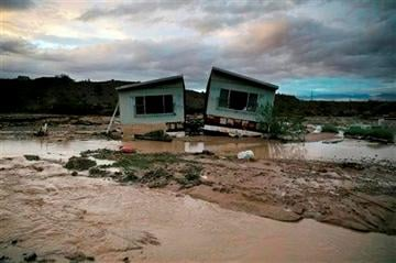 (AP Photo/John Locher,File). FILE - In this Monday, Sept. 8, 2014 file photo, receding flood water surrounds a home in Moapa, Nev.