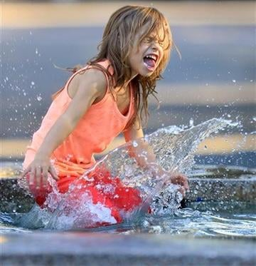 (AP Photo, Kent Porter, Santa Rosa Press Democrat). Five year-old Lydia Kobor of Sebastopol Ca., USA cools off in the Healdsburg, Ca., Plaza fountain, Thursday Oct. 2, 2014.