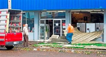 (AP Photo/The Daily News, John Markon). Technicians from Twin City Glass inspect wind damage at the entrance of the Manchester Brothers store on Vandercook Way, Thursday, Oct. 23, 2014 in Longview, Wash.