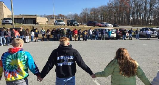 Search party conducts a prayer circle before continuing the search for Lilly Neff, 16