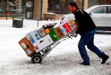 (AP Photo/Rapid City Journal, Chrfis Huber). Paul Nettles pushes his cart through the snow while delivering food to restaurants Monday morning, Nov. 10, 2014, in downtown Rapid City, S.D.