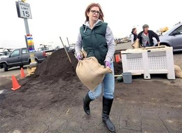 (AP Photo/The Press Democrat, Kent Porter). Cat Kaufman brings over a sand bag to protect her South A Street business, Wednesday Dec. 10, 2014 in Santa Rosa, Calif.